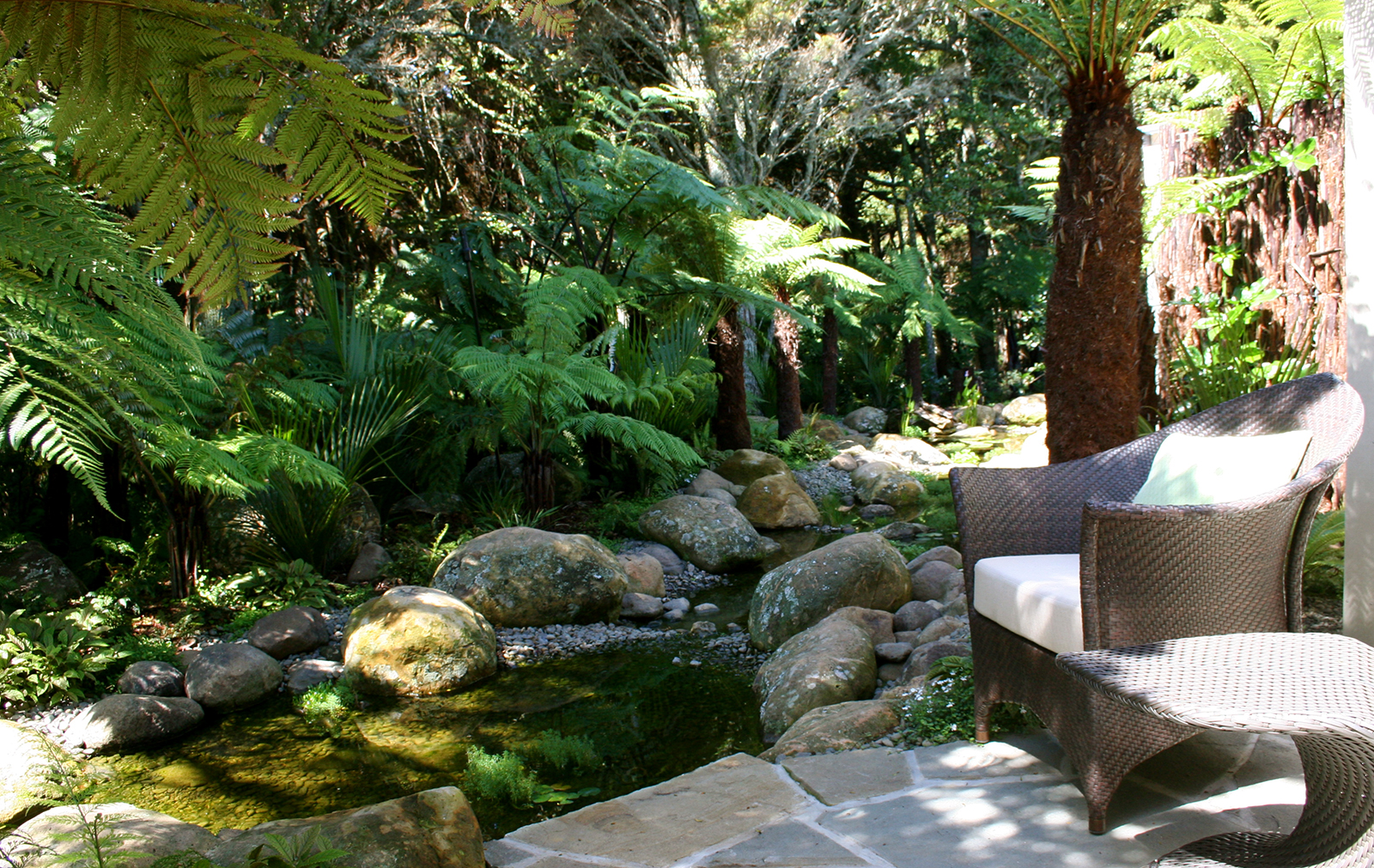Relax amongst the subtropical plantings and rocky stream